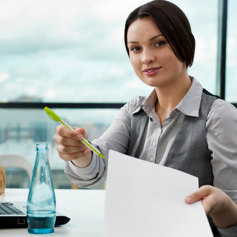 Woman with dark hair handing pen and paper to someone, desk and vase on desktop, window in background