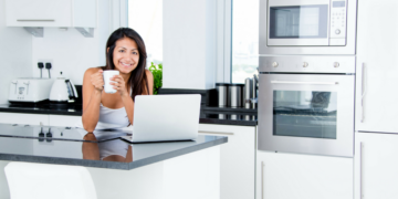 Kitchen with white cabinets, stainless steel microwave and oven, black countertops. woman sitting at island drinking from mug while sitting in front of laptop