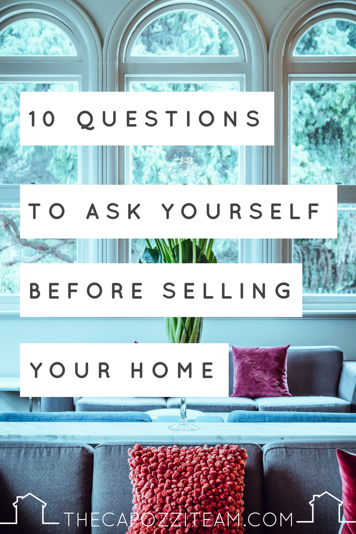 """Living room with grey couch, pink hued pillows, white walls with arched windows and vase of greenery, text reads """"10 Questions to ask yourself before selling a home"""" """"TheCapozziTeam.com""""; The Capozzi Team logo on pillow"""