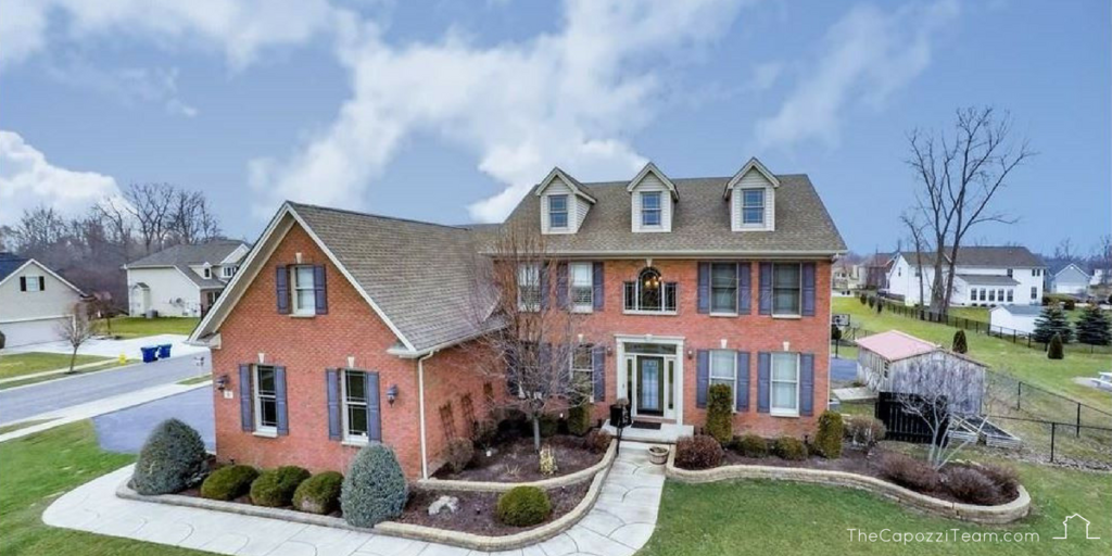 Essex model 2 story brick home with blue shutters, 6 Pennington Ct Amherst NY 14228, text reads thecapoziteam.com