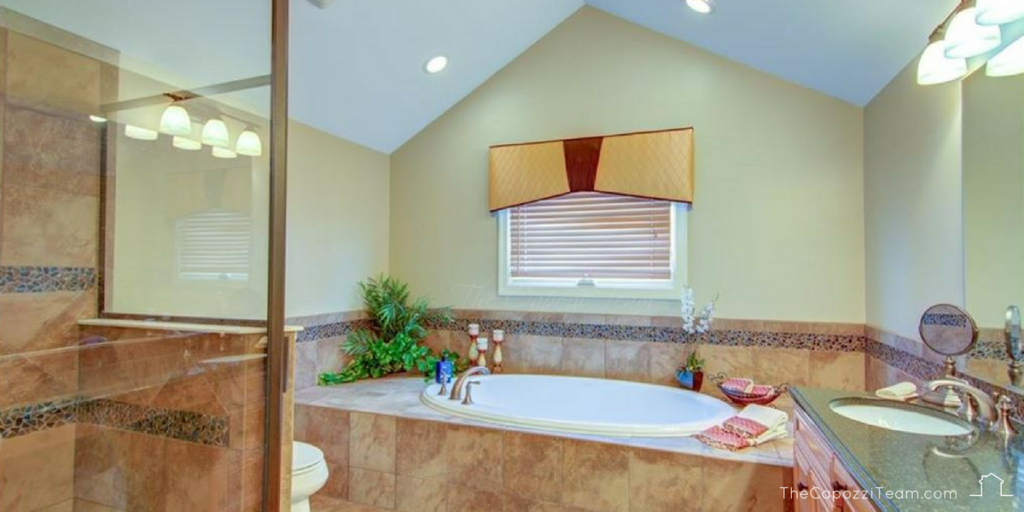 Bathroom suite with Jacuzzi tbu, shower stall and vanity, text reads thecapozziteam.com